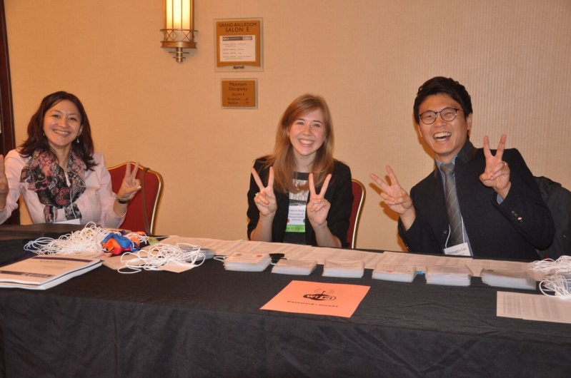 Three happy registration desk volunteers