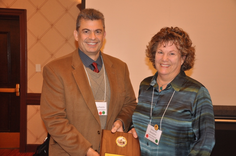 Thanos Patelis presents Distinguished Mentoring Award to Debbi Bandalos